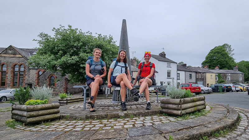 3 girls sat at start of Cumbria Way