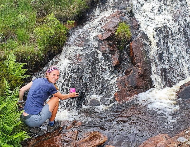 Person filling up water from waterfall