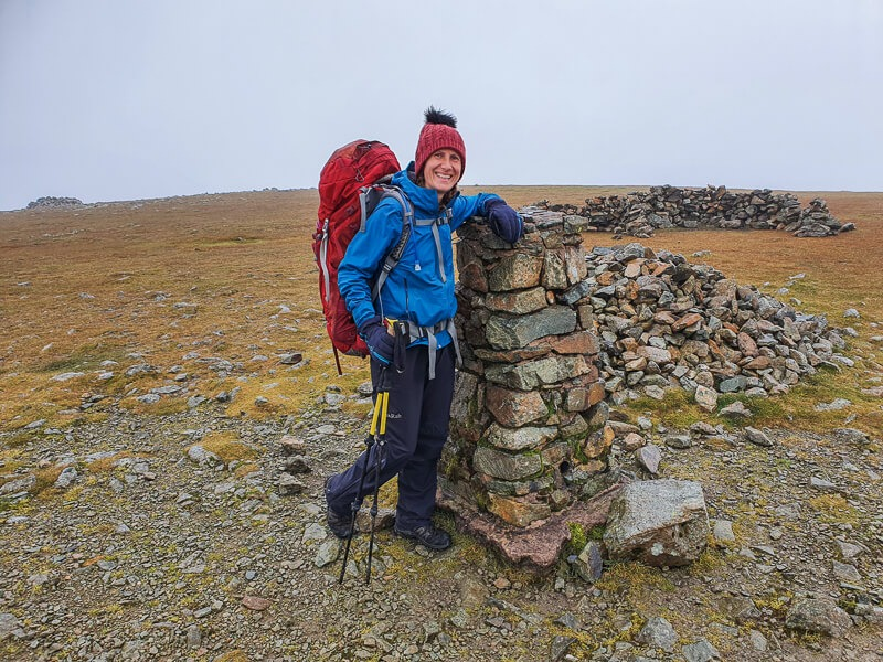 Stood next to stone trig wearing backpack