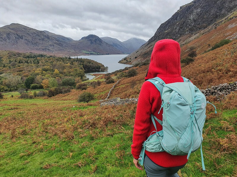 Standing wearing hoody and backpack looking at views