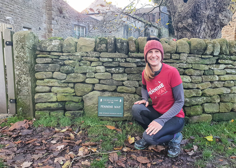 Becky wearing Pennine Way t-shirt next to sign