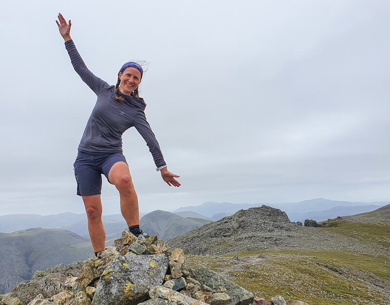 Becky stood on stone cairn wearing Salomon top and shorts