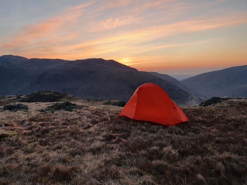 Orange tent on a hill wild camp spot