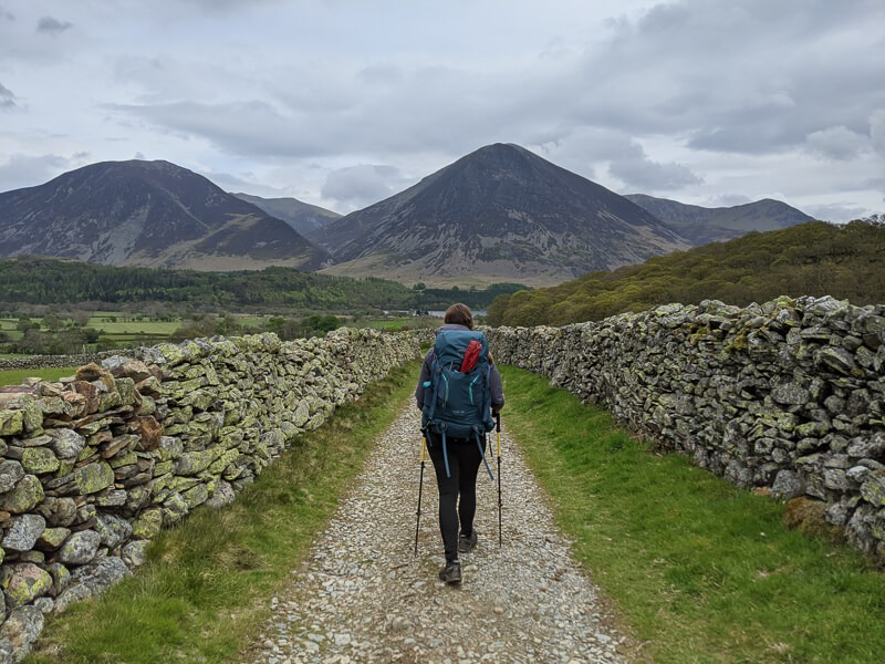 Becky walking with backpack mountain in front