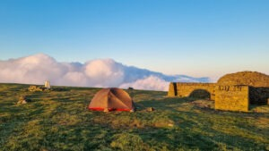Wild camping on hill with tent and clouds